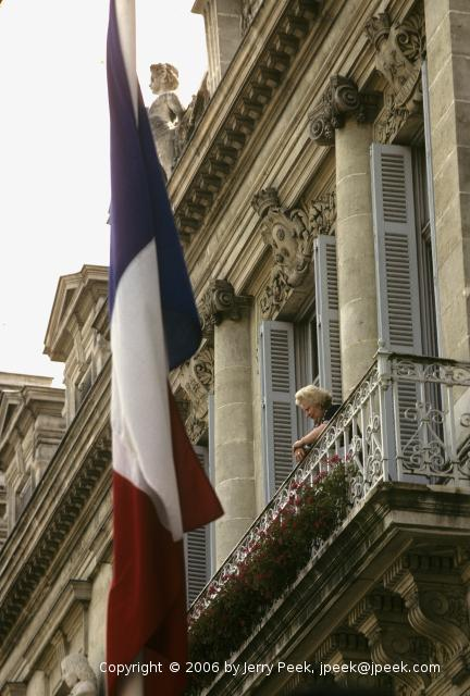 woman watches parade from her balcony over Place Verdun