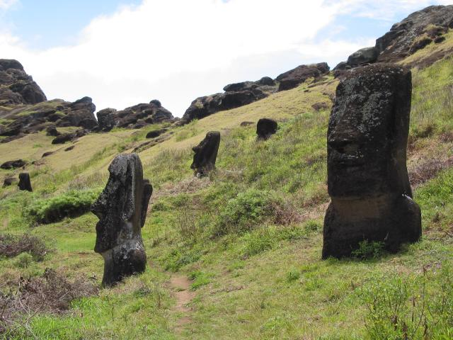 Two moai in foreground, more -- and cliffs -- in background