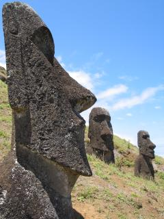 Moai face in profile at left edge, two more in background