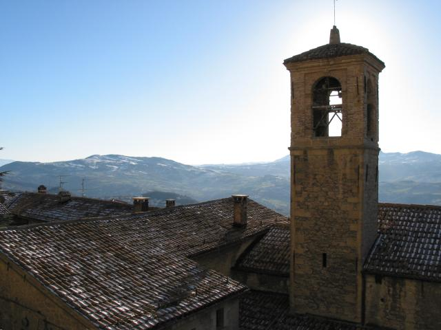 Roofs, sun behind bell tower, and distant mountains