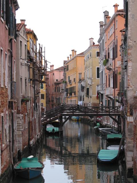 Canal, bridge between buildings, and boats