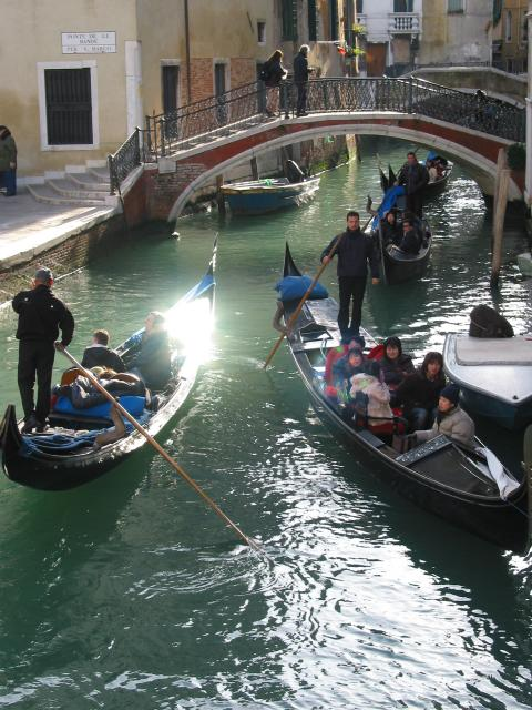 Gondoliers and bridge with a sunny reflection