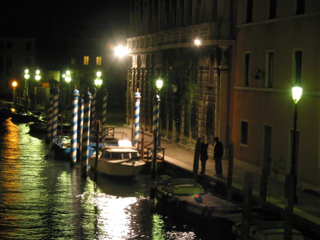 Nighttime view of people and boats under lamps, Venezia