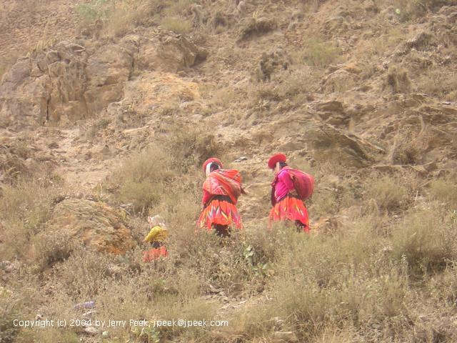 Three people in bright-colored clothes walking up a path, Ollantaytambo, Peru