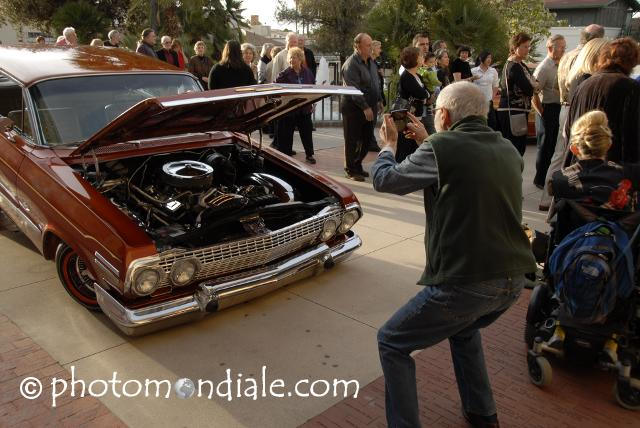 Man photographs engine of low-rider Chevy, Tucson Museum of Art plaza