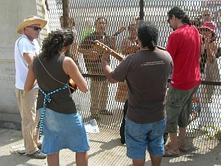 Musicians playing together across the border fence