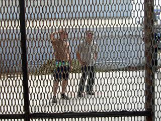 Two men looking at border fence from Mexican side